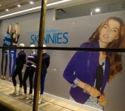"""""""Magic Fabric"""" is a removable adhesive that is easier to install and does not leave residue or damage wall when removed. Here image is printed & then digitally die cut to shape for big impact in window display."""